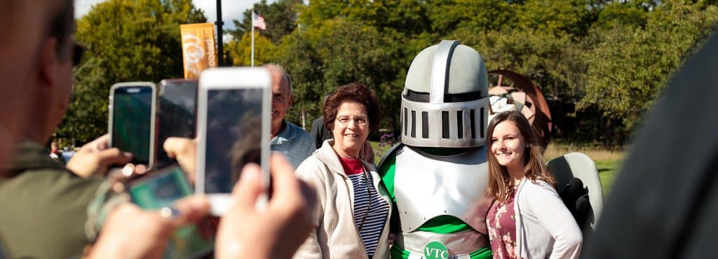 alumni guests smile for camera, knight mascot