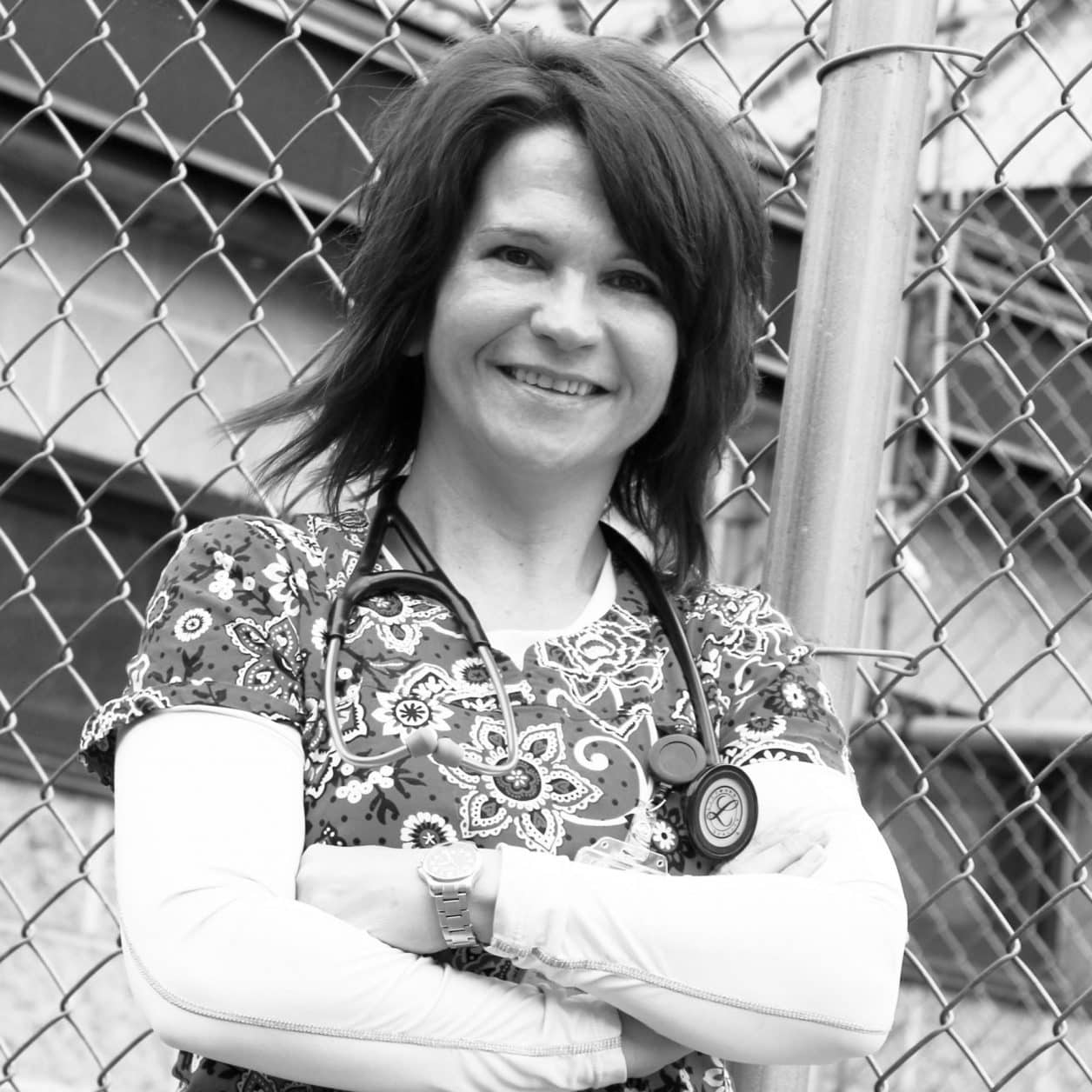 Female student, standing outside, arms crossed, nurse, stethoscope, smiling