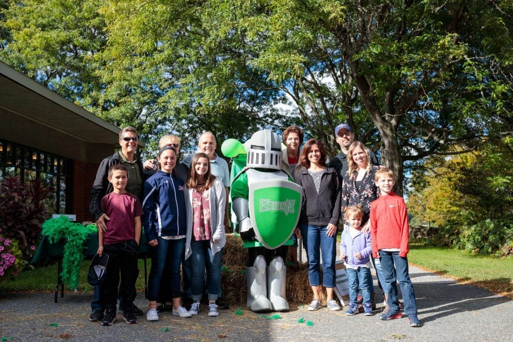 alumni homecoming, VTC Knight mascot, outside, smiling, group of visitors