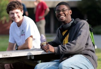 Male students, sitting outside on picnic table, ice cream, smiling