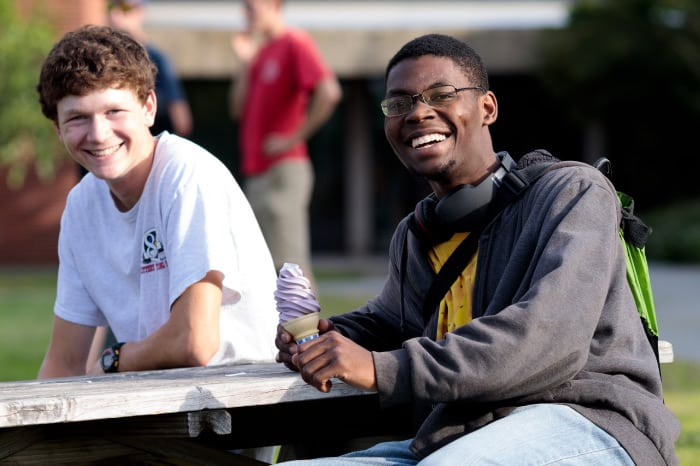 male students, sitting at picnic table, smiling, ice cream, diversity