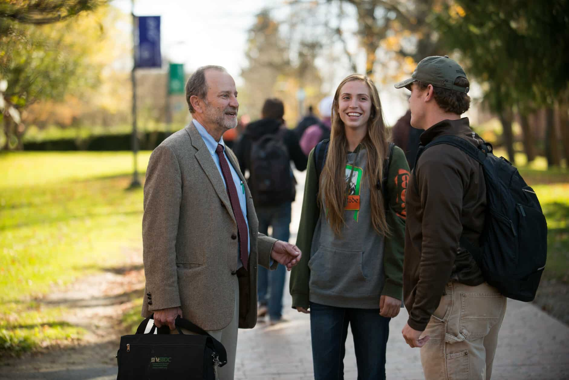 Professor talks with students, faculty, female student, male student, walkway, chatting, Randolph Center campus