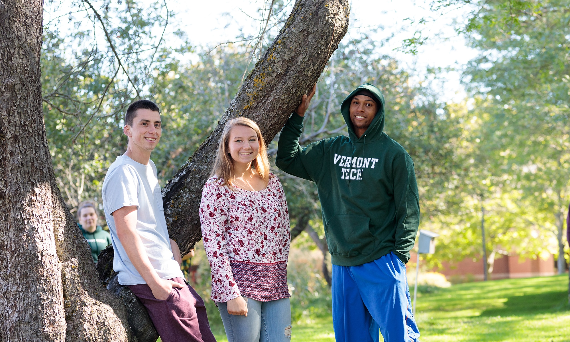 three students stand among the apple trees on the Randolph Center campus