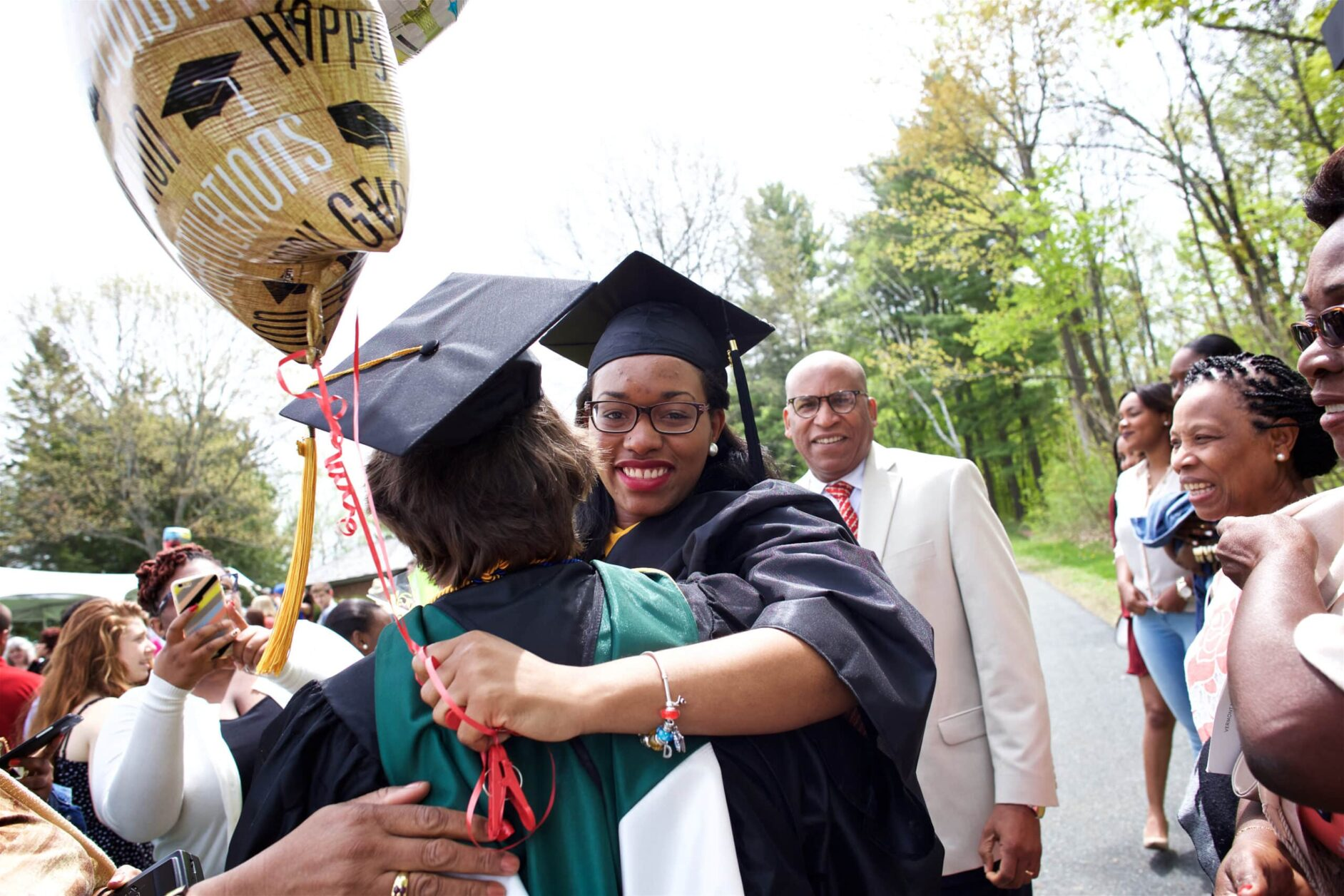Two young women in graduation gowns hug holding balloons, onlookers smile behind