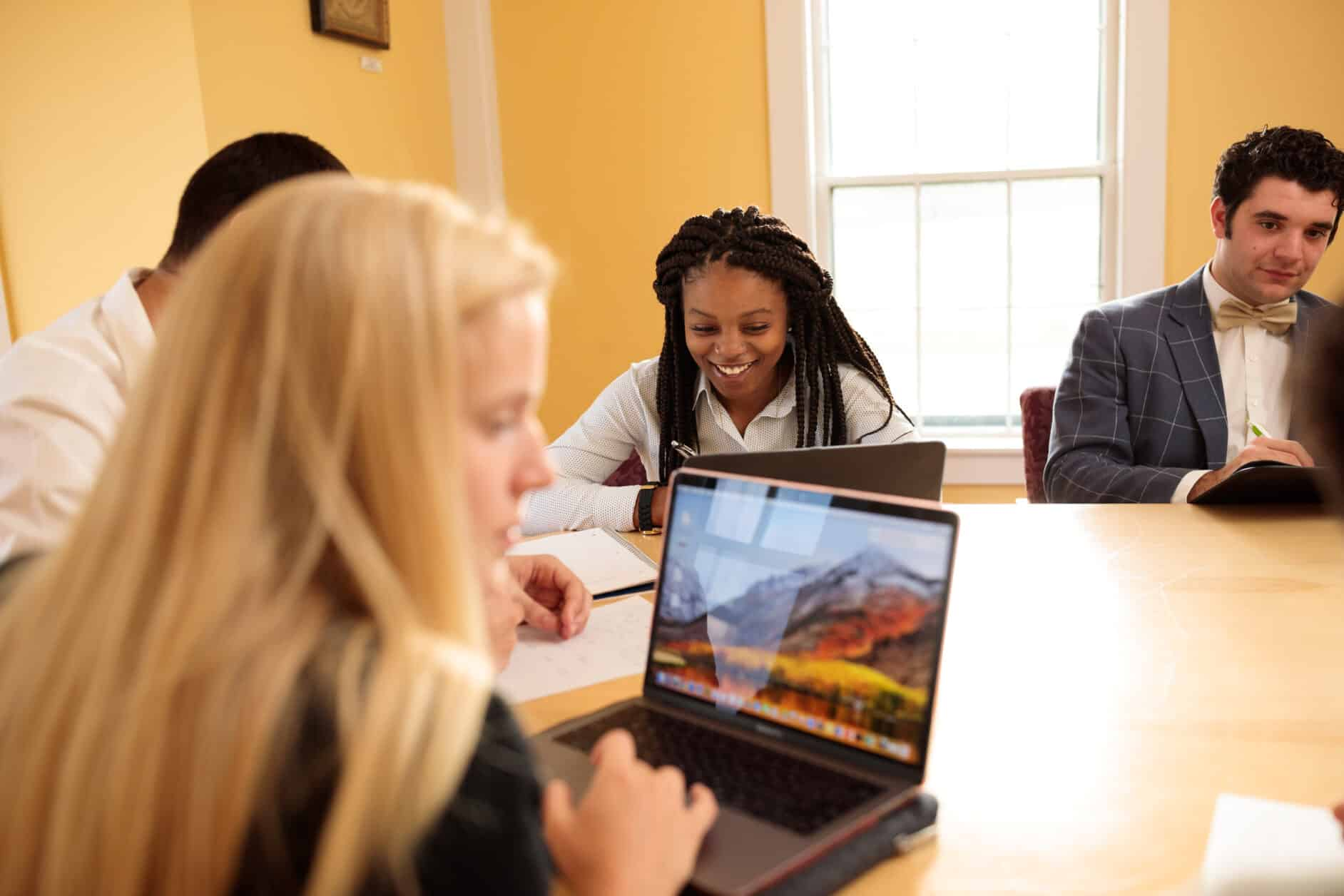 Business students sit around a yellow conference table working on laptops